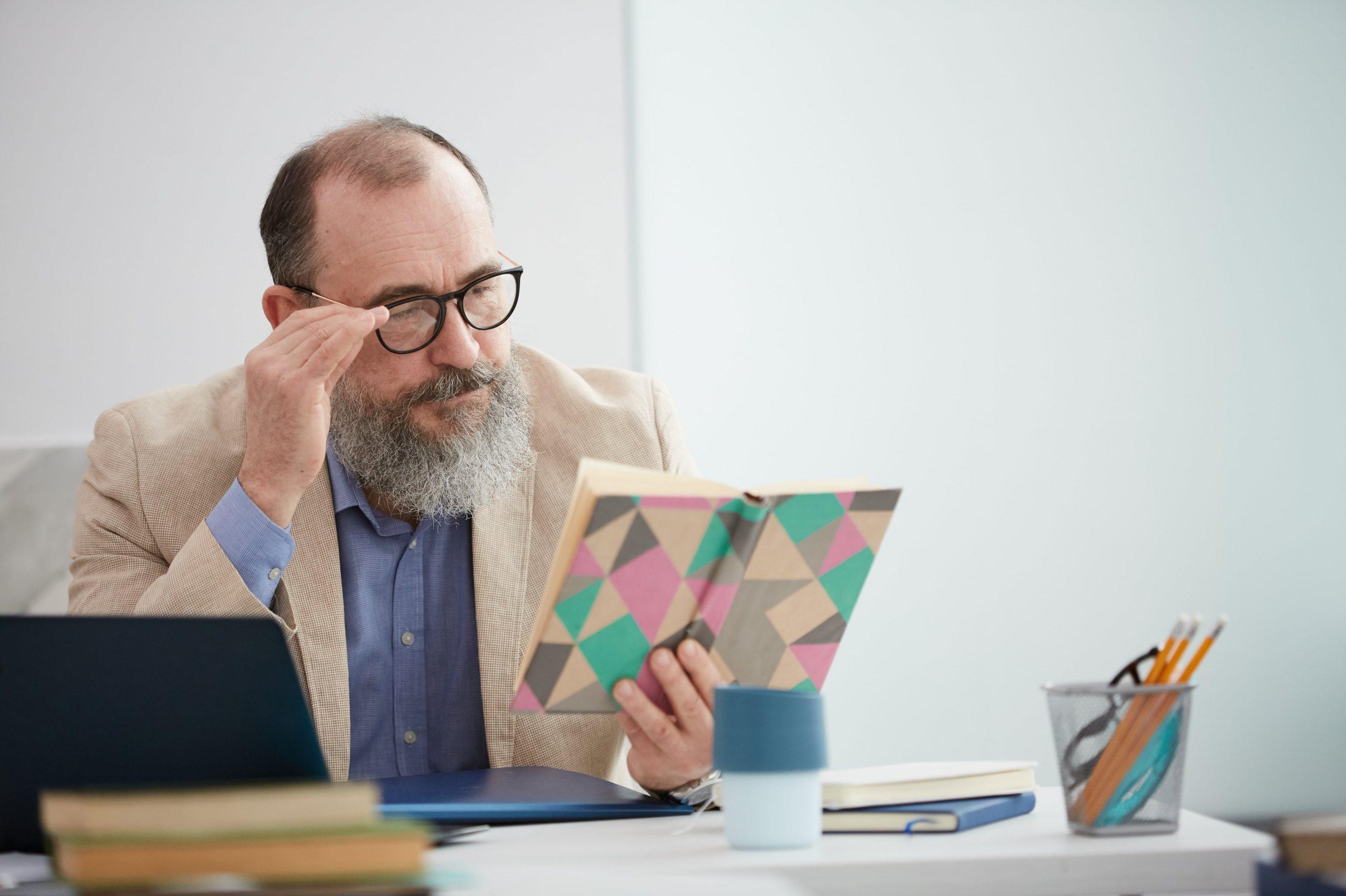 bearded-senior-teacher-at-desk-CKRZKEN-min