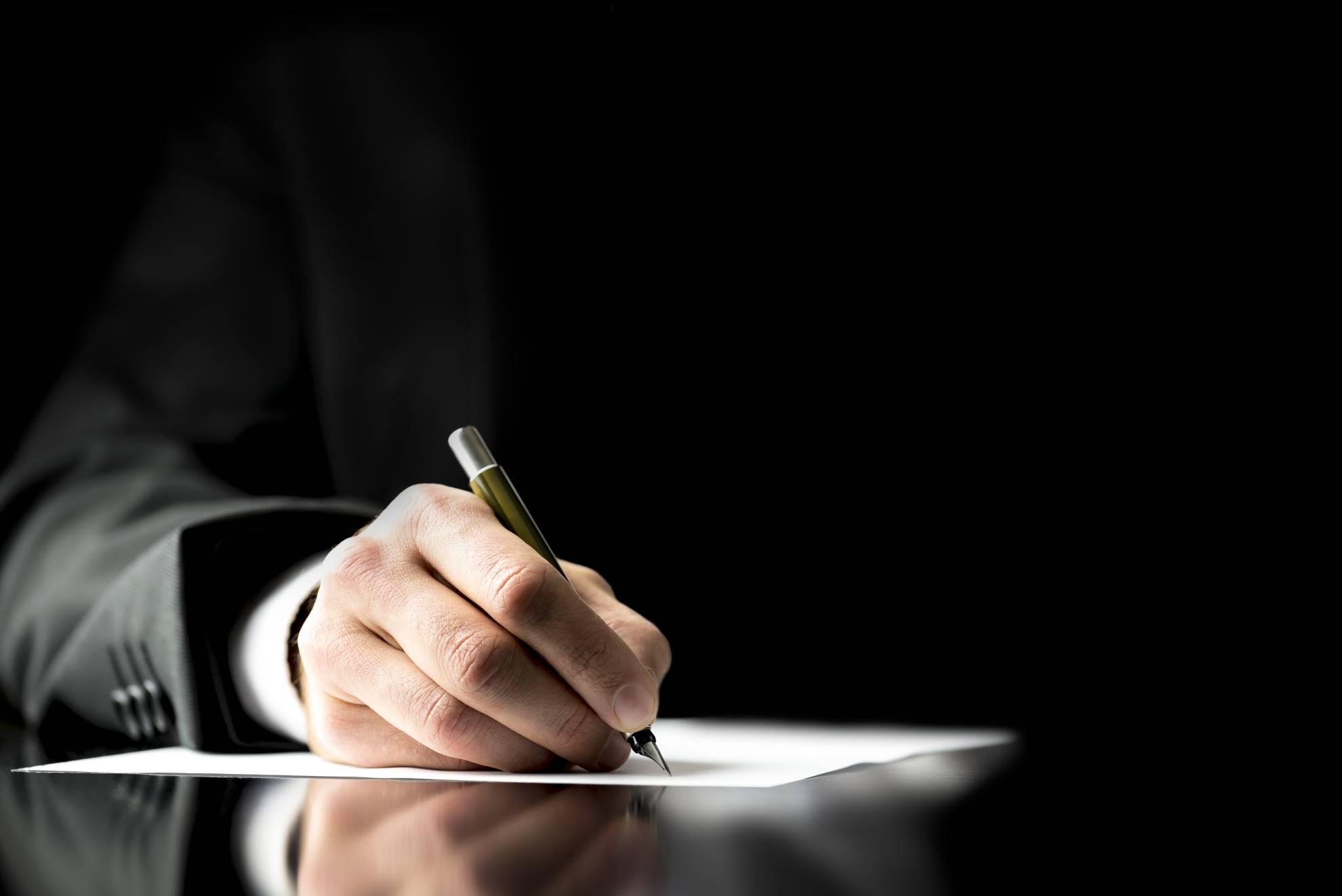 businessman-signing-a-document-DDFVSS9 (1)