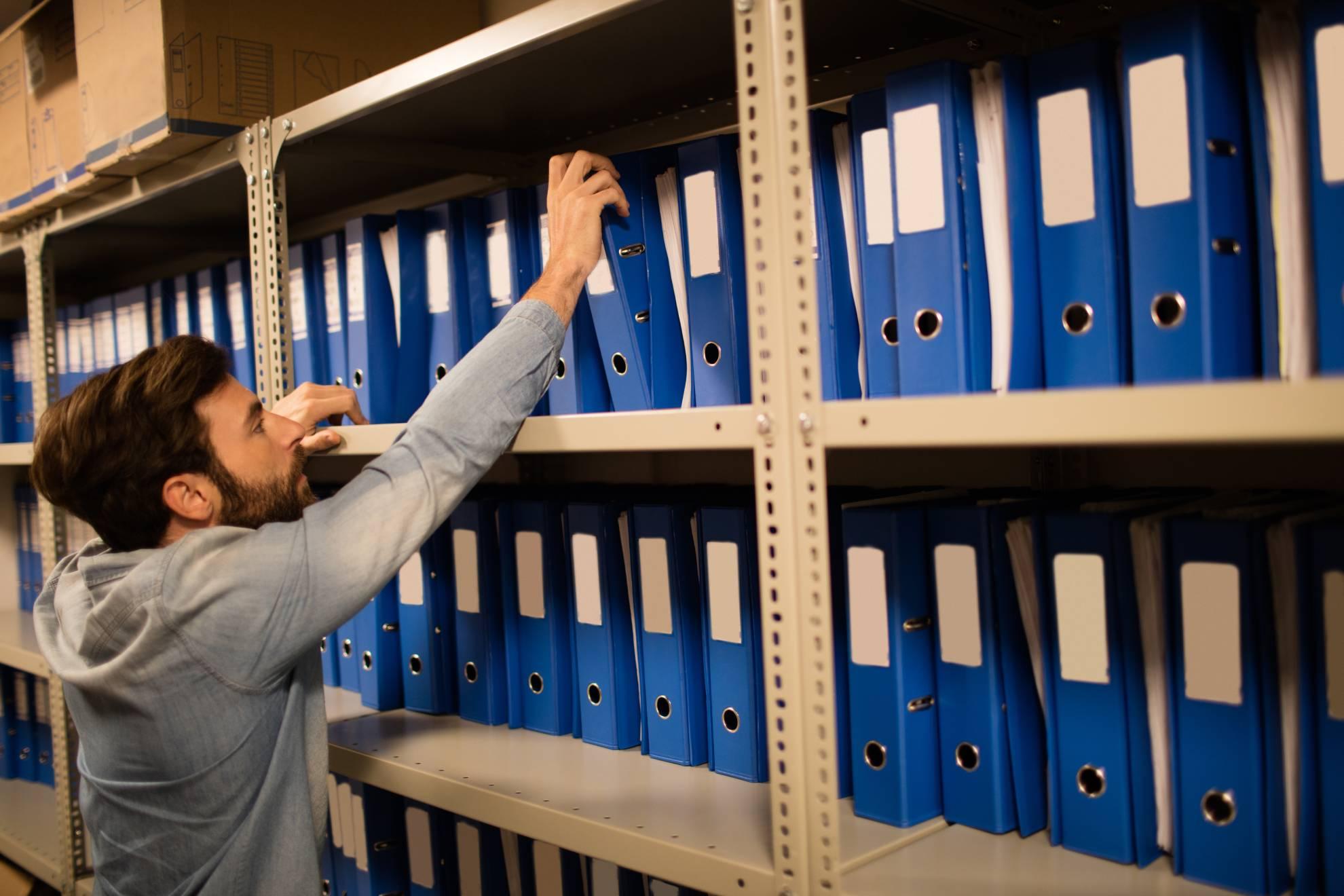 businessman-taking-file-from-shelf-in-storage-room-6RYKWWV (1)