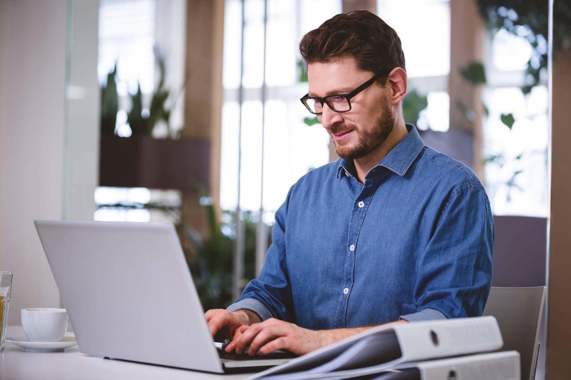 confident-businessman-working-on-laptop-at-creativ-ULR2F3K (1)