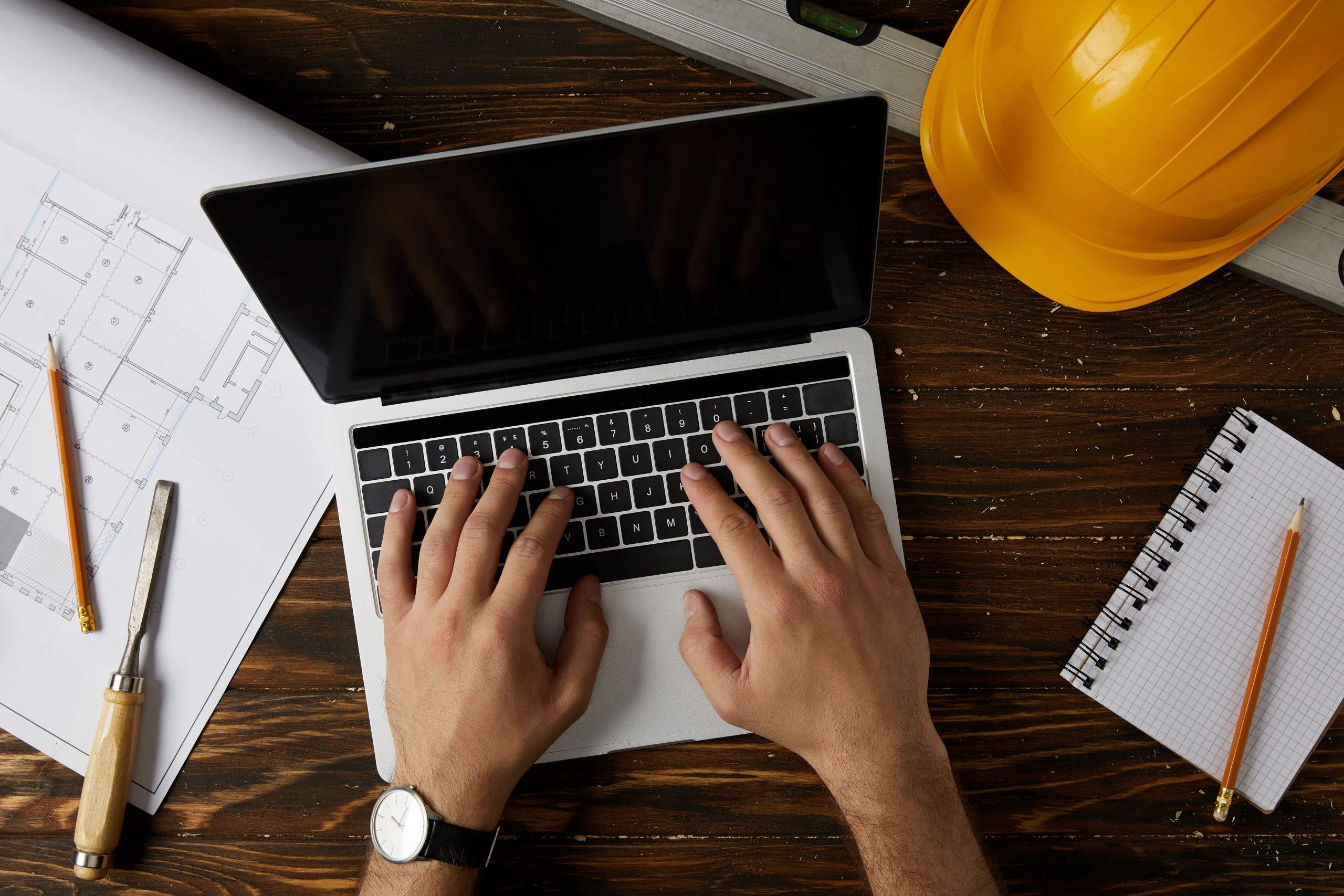 cropped-image-of-architect-typing-on-laptop-at-tab-5CRFP3J-min