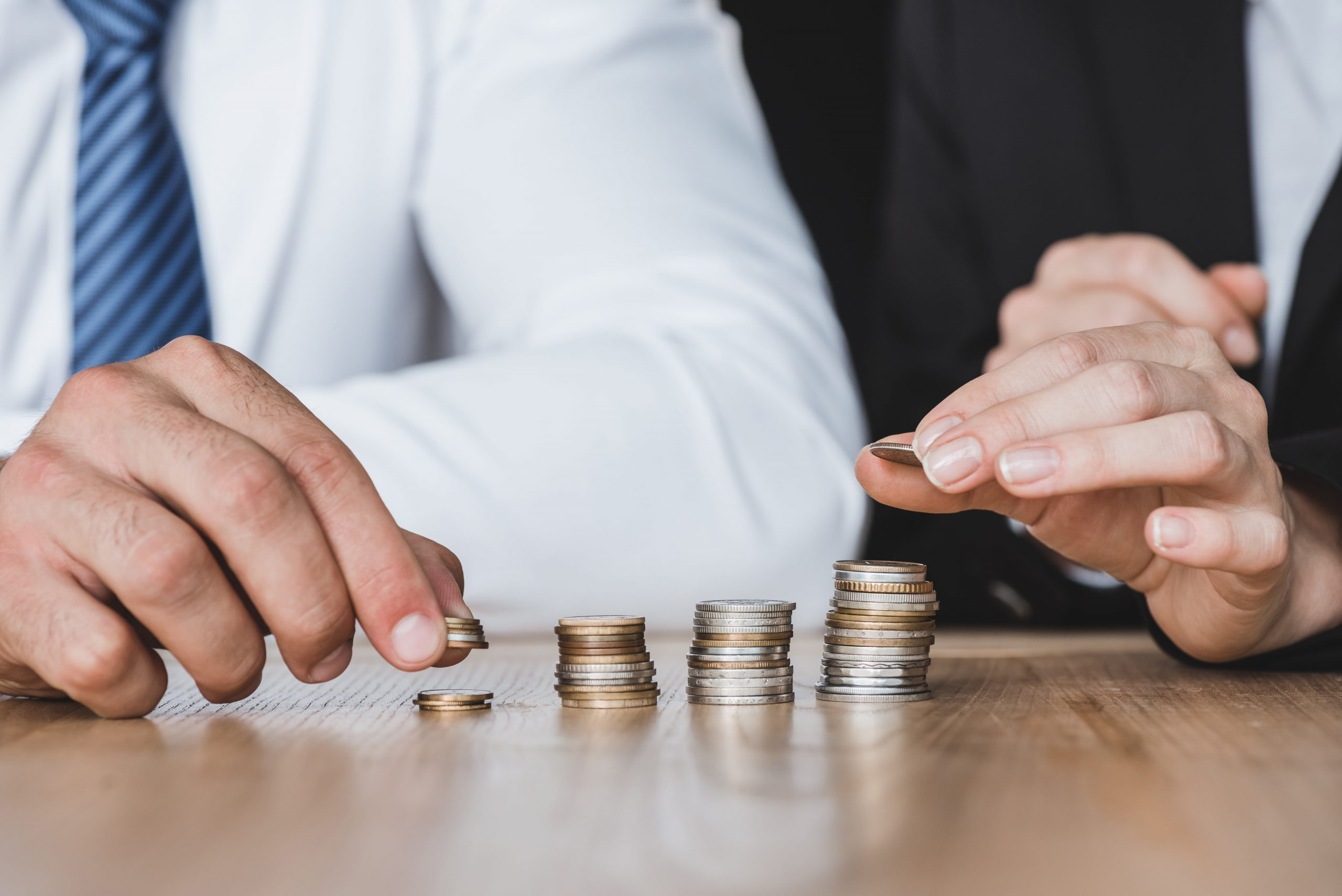 cropped-image-of-financiers-stacking-coins-on-tabl-VAAAWAP-min