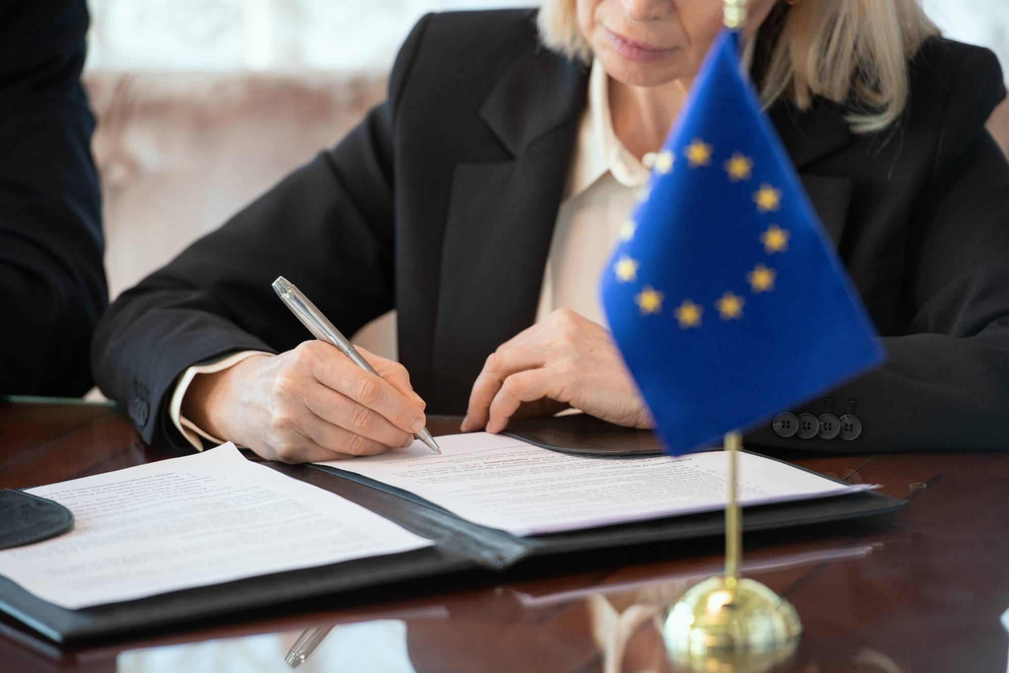 flag-of-european-union-on-table-against-mature-fem-EWKTE5E (1)