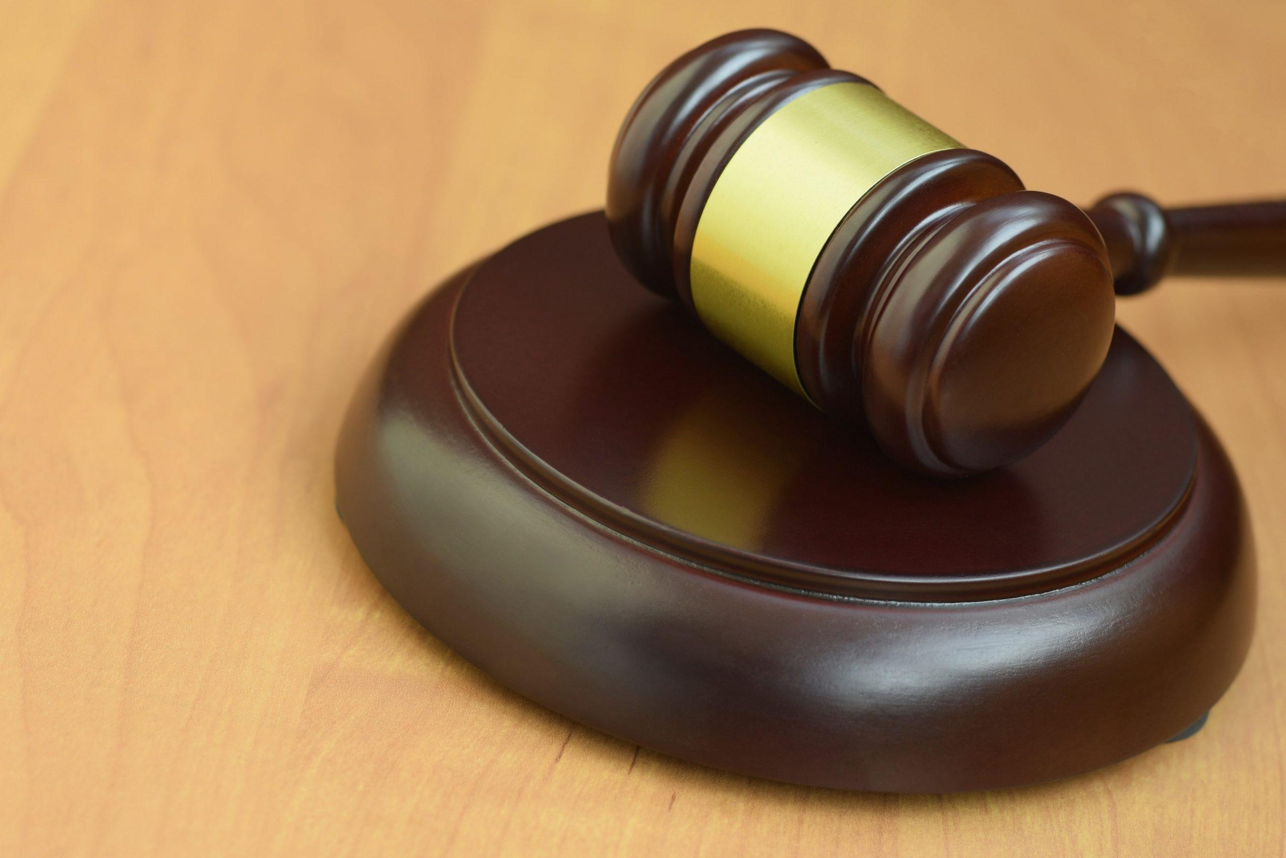 justice-mallet-on-wooden-desk-in-a-courtroom-durin-DLHAM3D-min