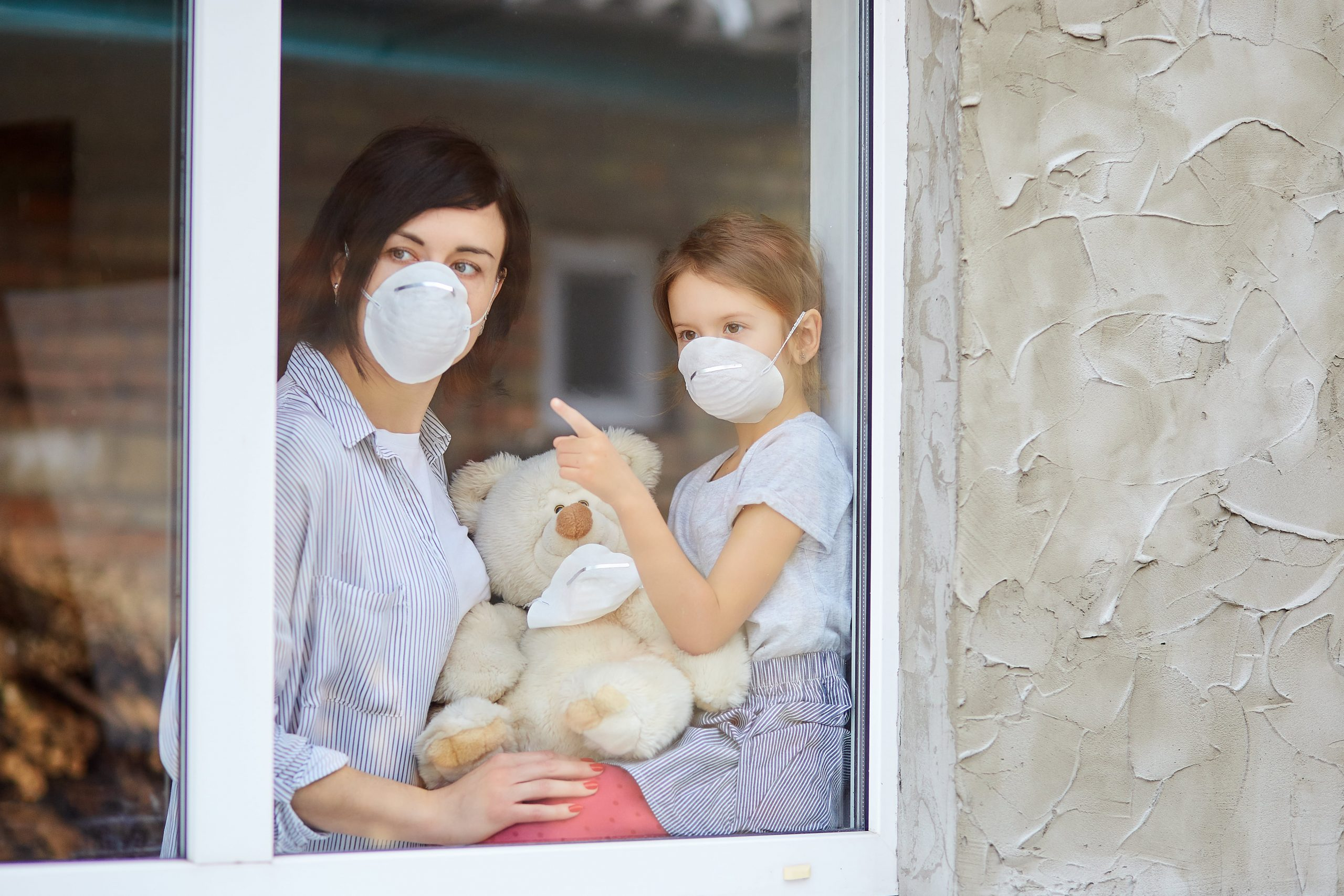 mother-with-daughter-child-in-mask-looking-from-wi-4YJJWX7-min