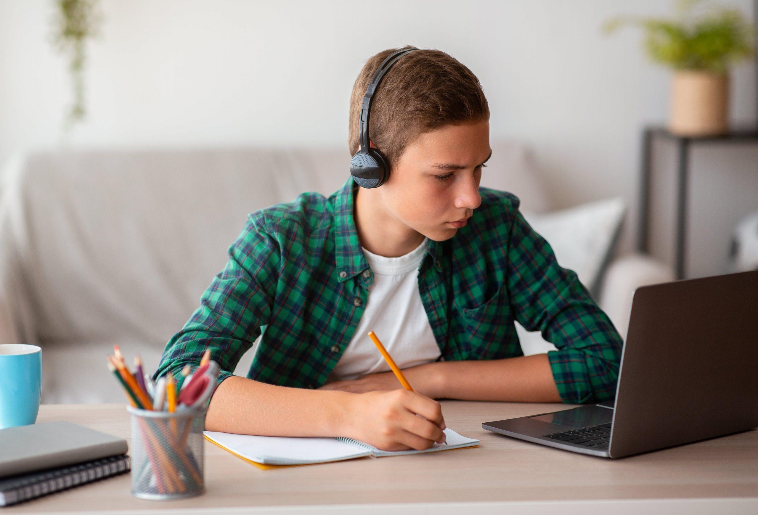 pensive-school-boy-with-earphones-studying-online–XXEV6ED-min
