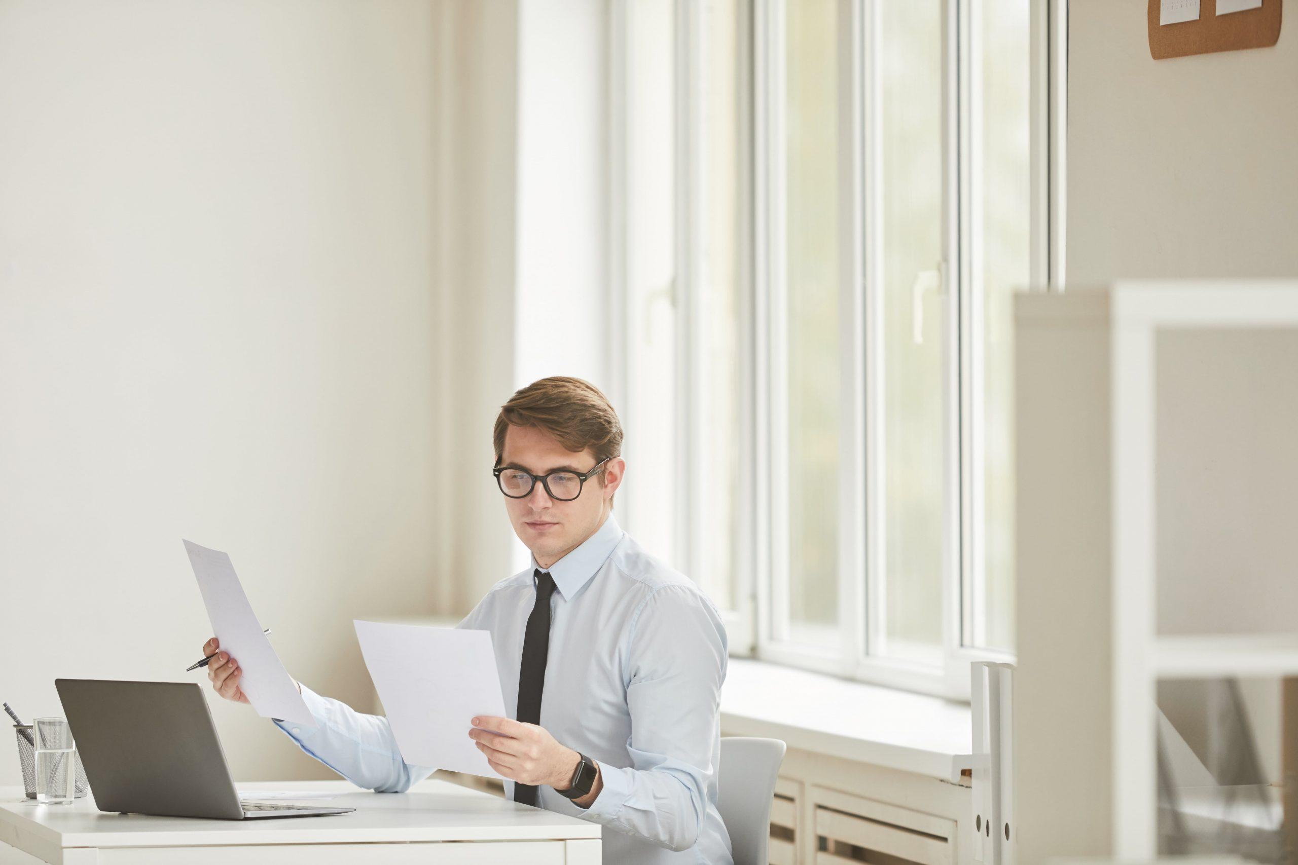 successful-businessman-reading-documents-at-desk-6SAYA9V-min