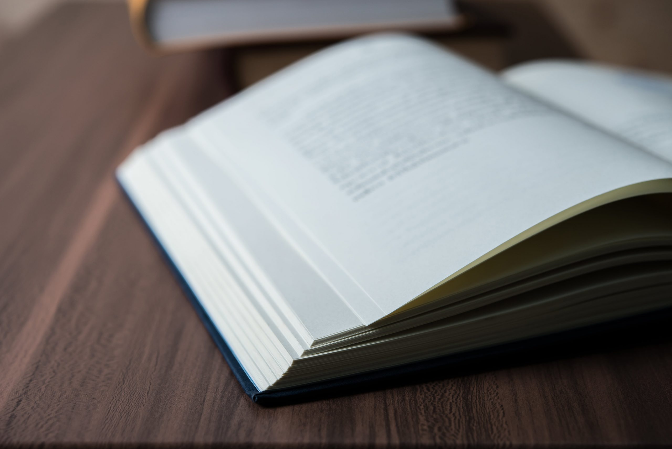 close-up-of-opened-book-on-wooden-table-education–M9DTS2V