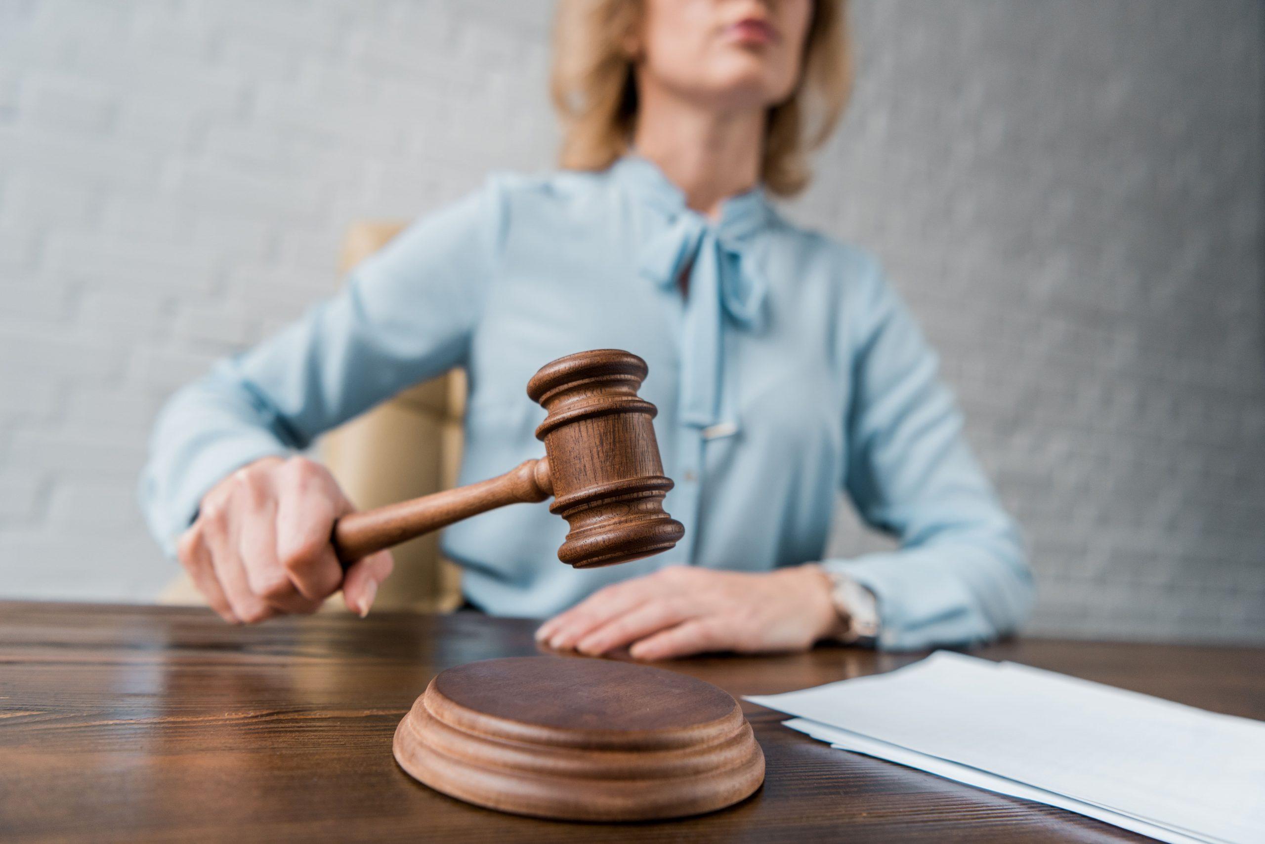 cropped-shot-of-female-judge-holding-wooden-hammer-ZLF37XG