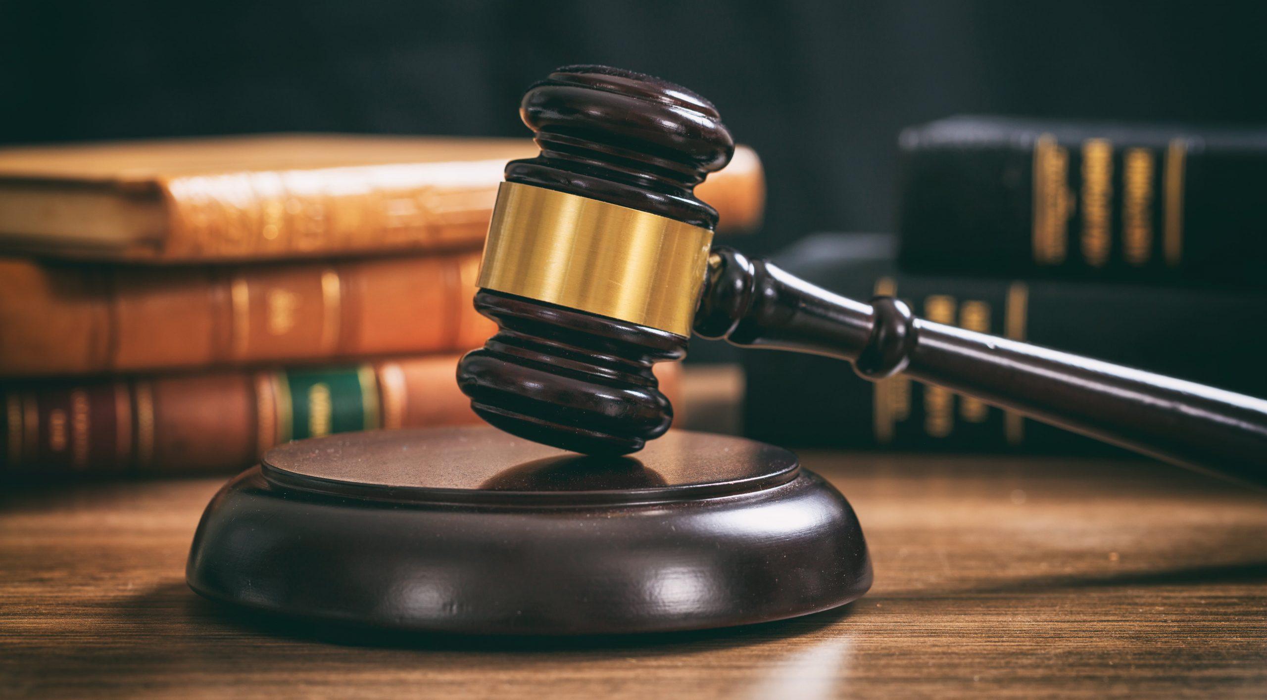 judge-gavel-on-a-wooden-desk-law-books-background-PLECUPQ-min
