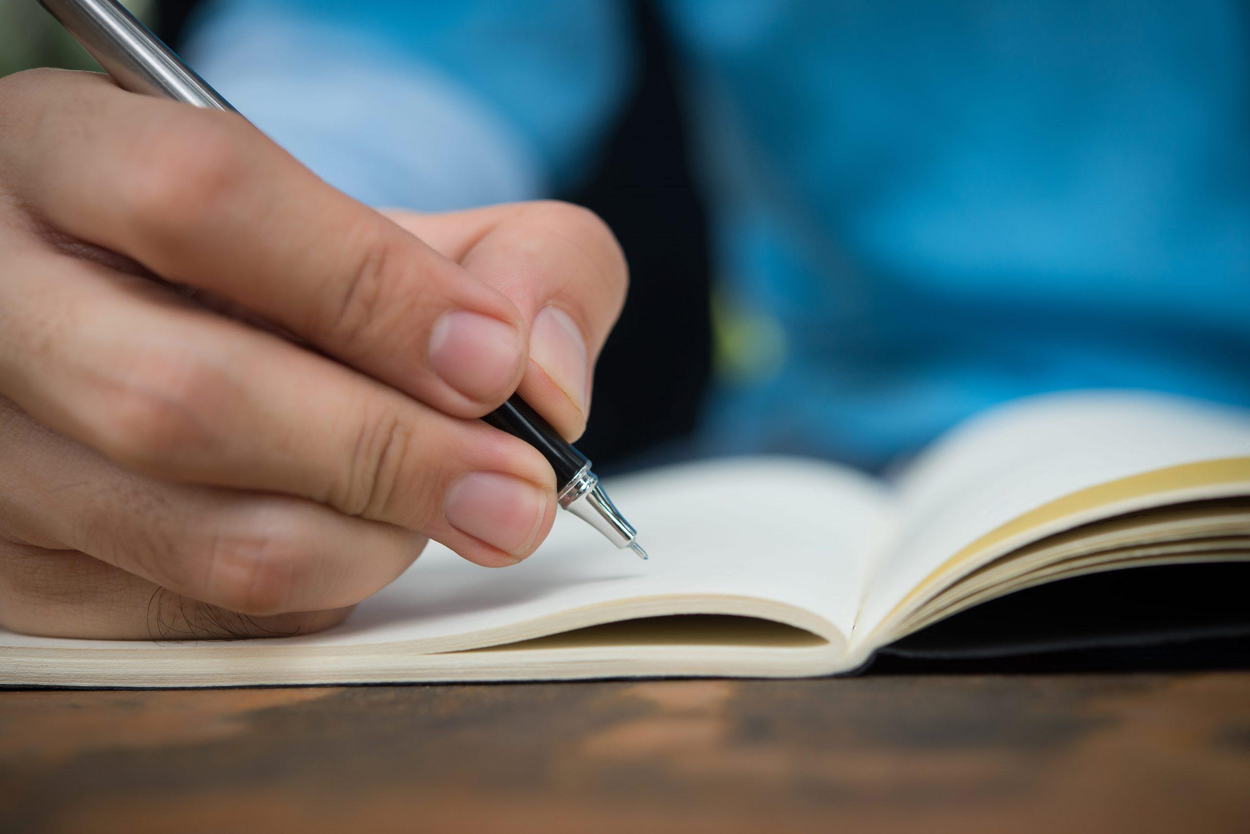 man-hand-write-on-the-notebook-PVXM5DA