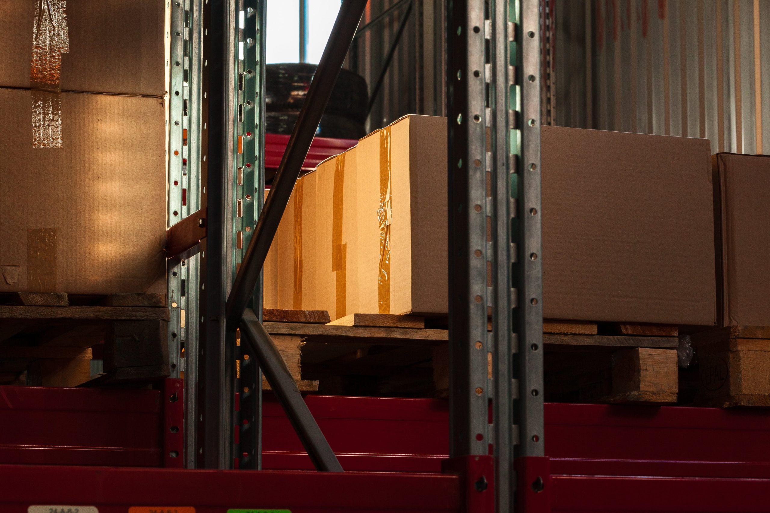 modern-warehouse-shelves-with-pile-of-cardboard-bo-YQ3THAA