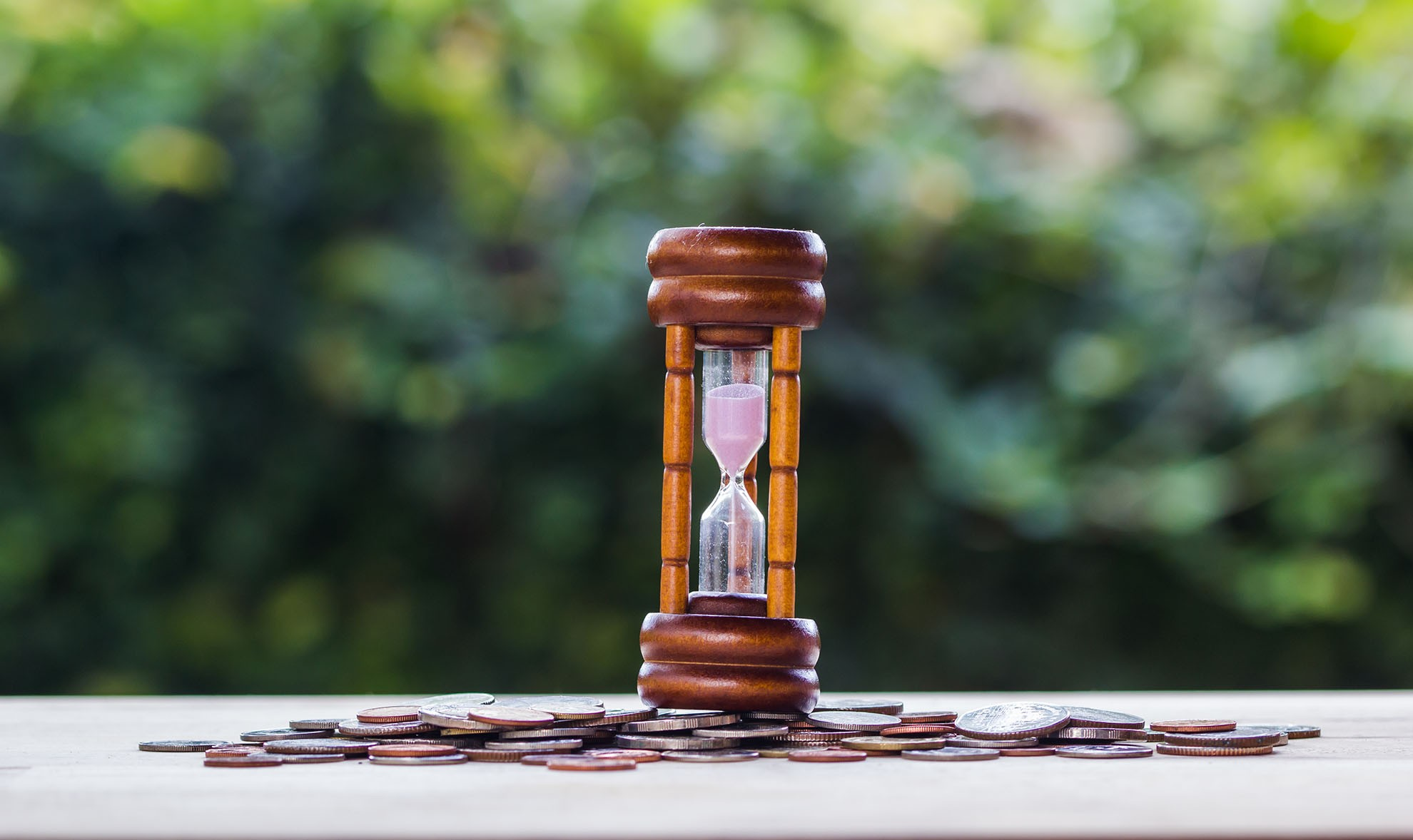 Hourglass on stack coins on with blurred nature background on wo