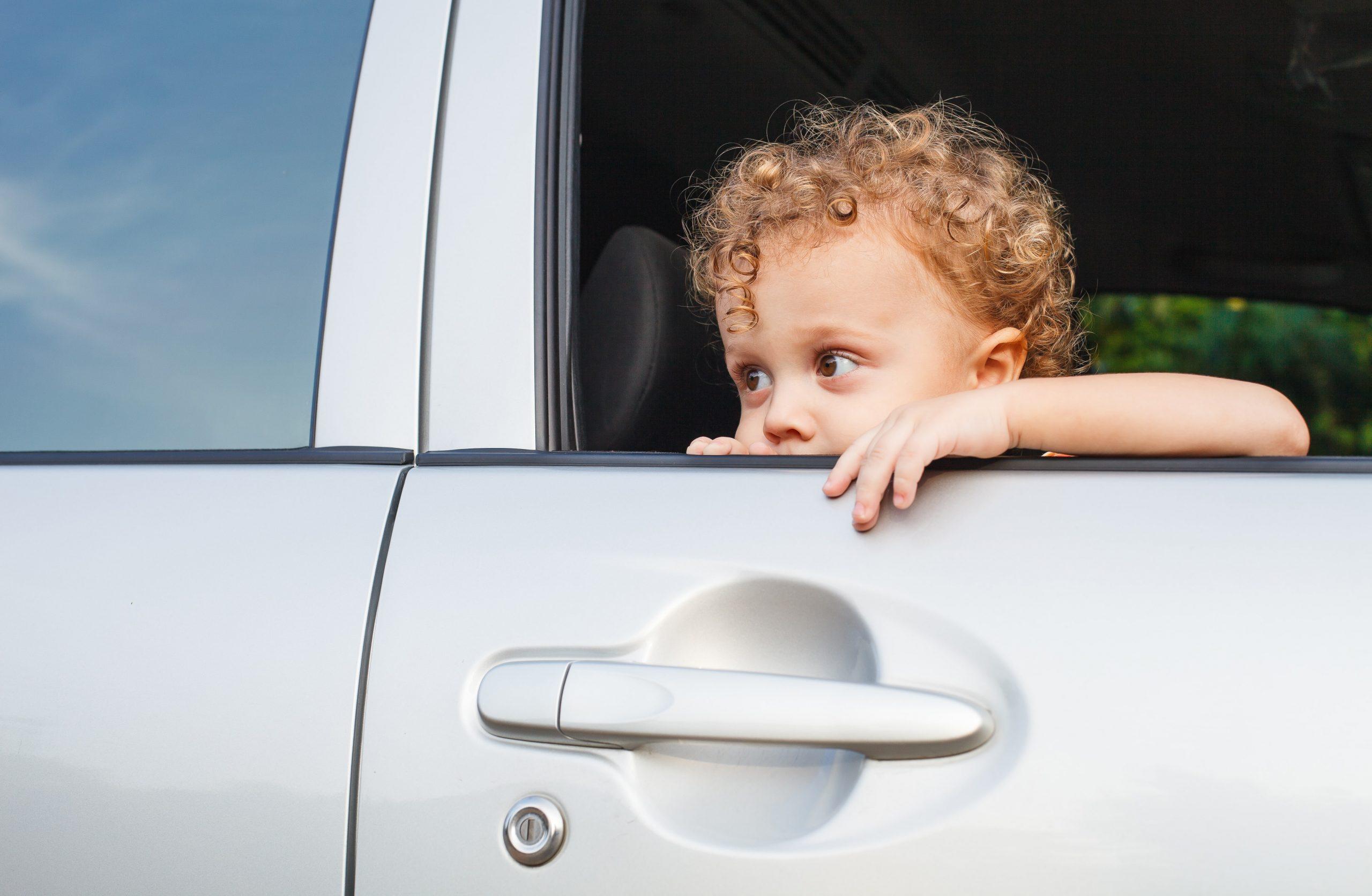 sad-boy-near-car-window-UA89XMZ