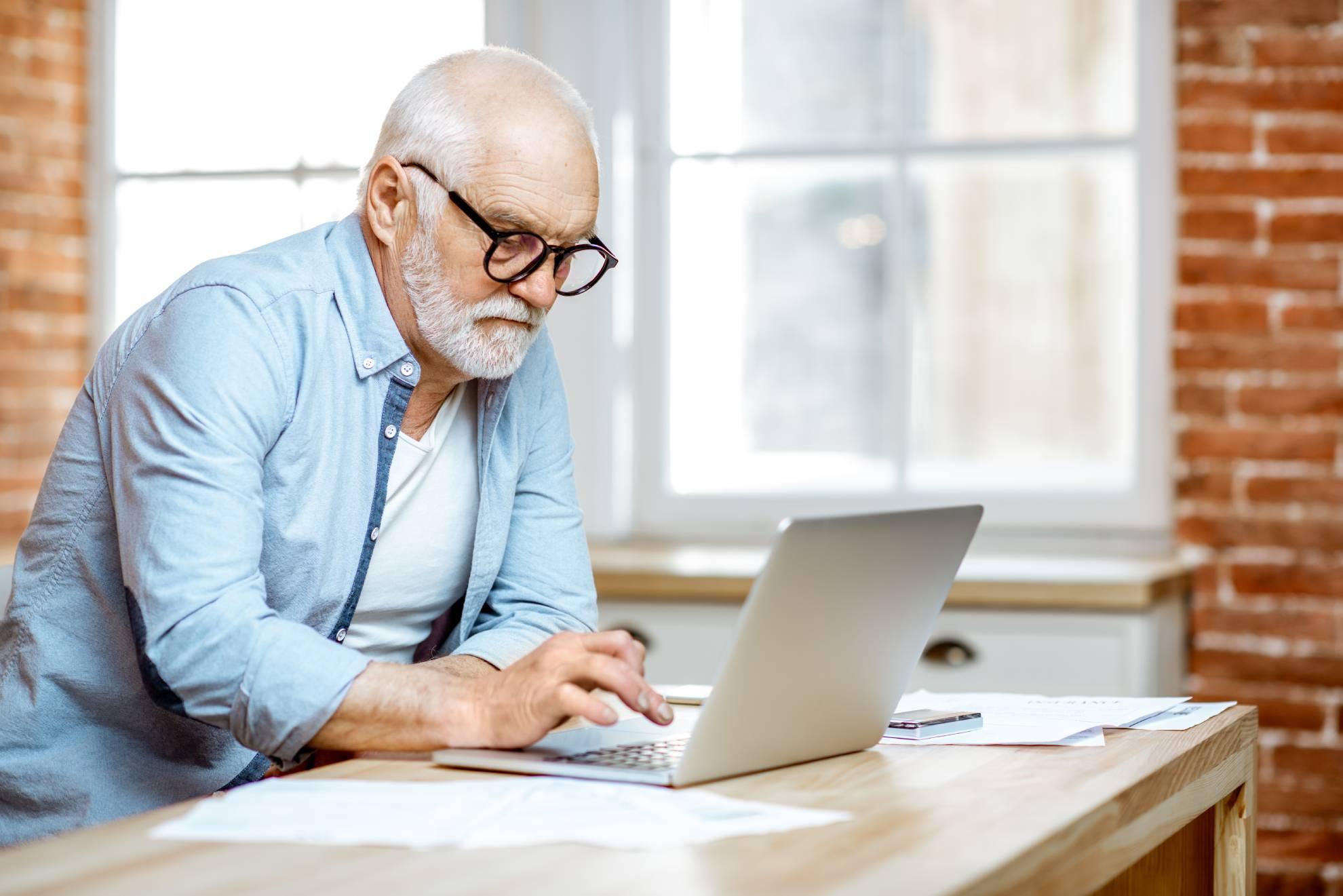 senior-man-with-laptop-at-home-AUWYQLU (1)