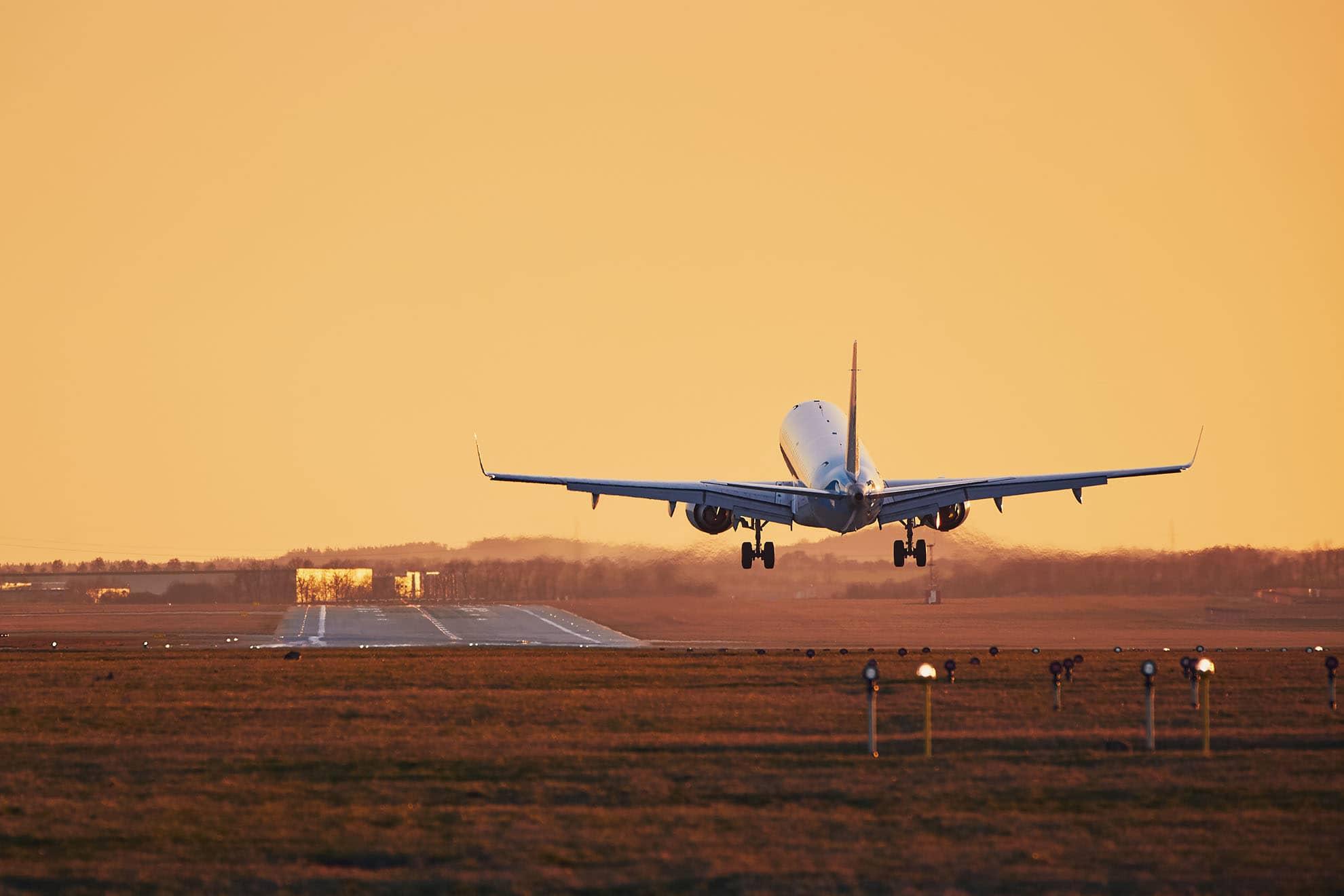 airplane-landing-at-sunset-LX8TSWZ-min