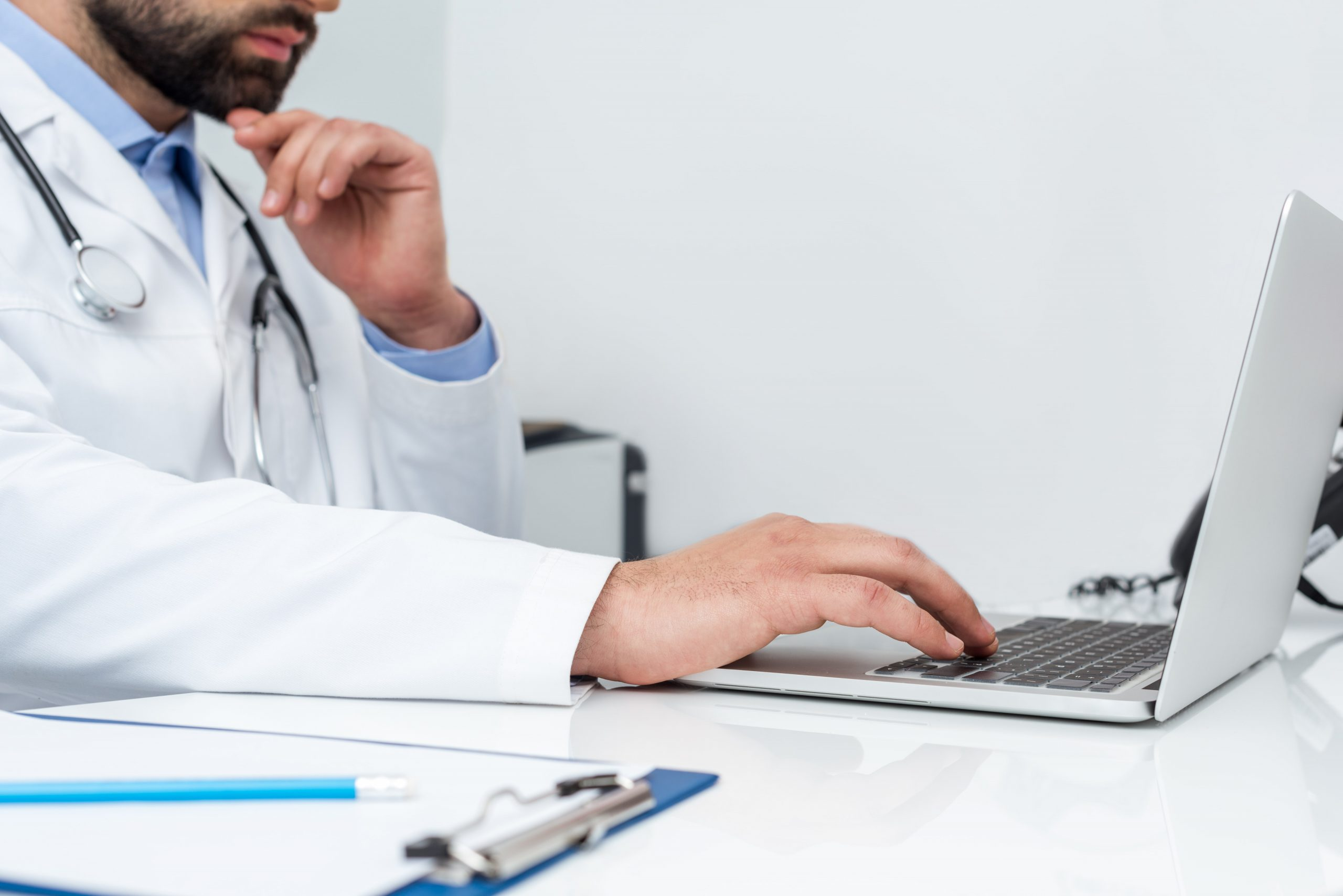 cropped-shot-of-doctor-using-laptop-at-workplace-P2QZMRQ