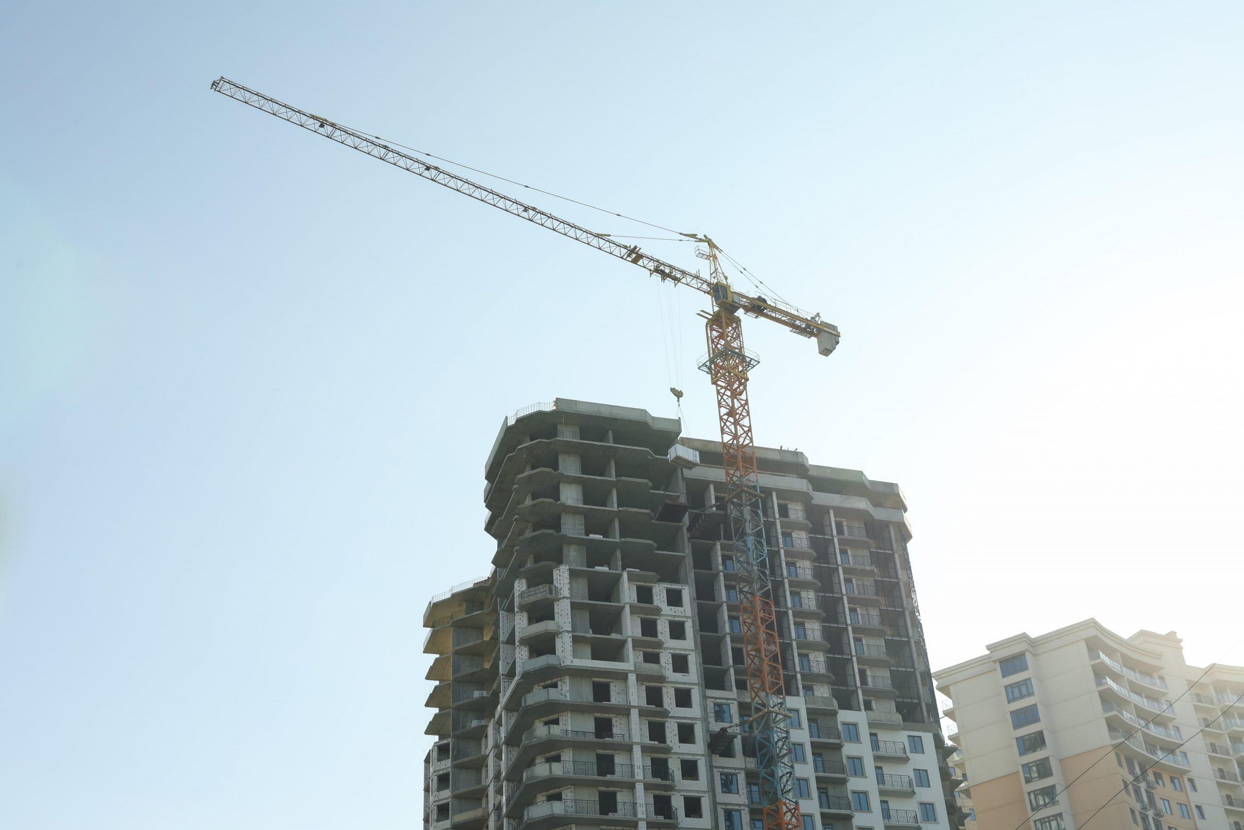 high-rise-construction-with-crane-against-blue-sky-C8LHC77