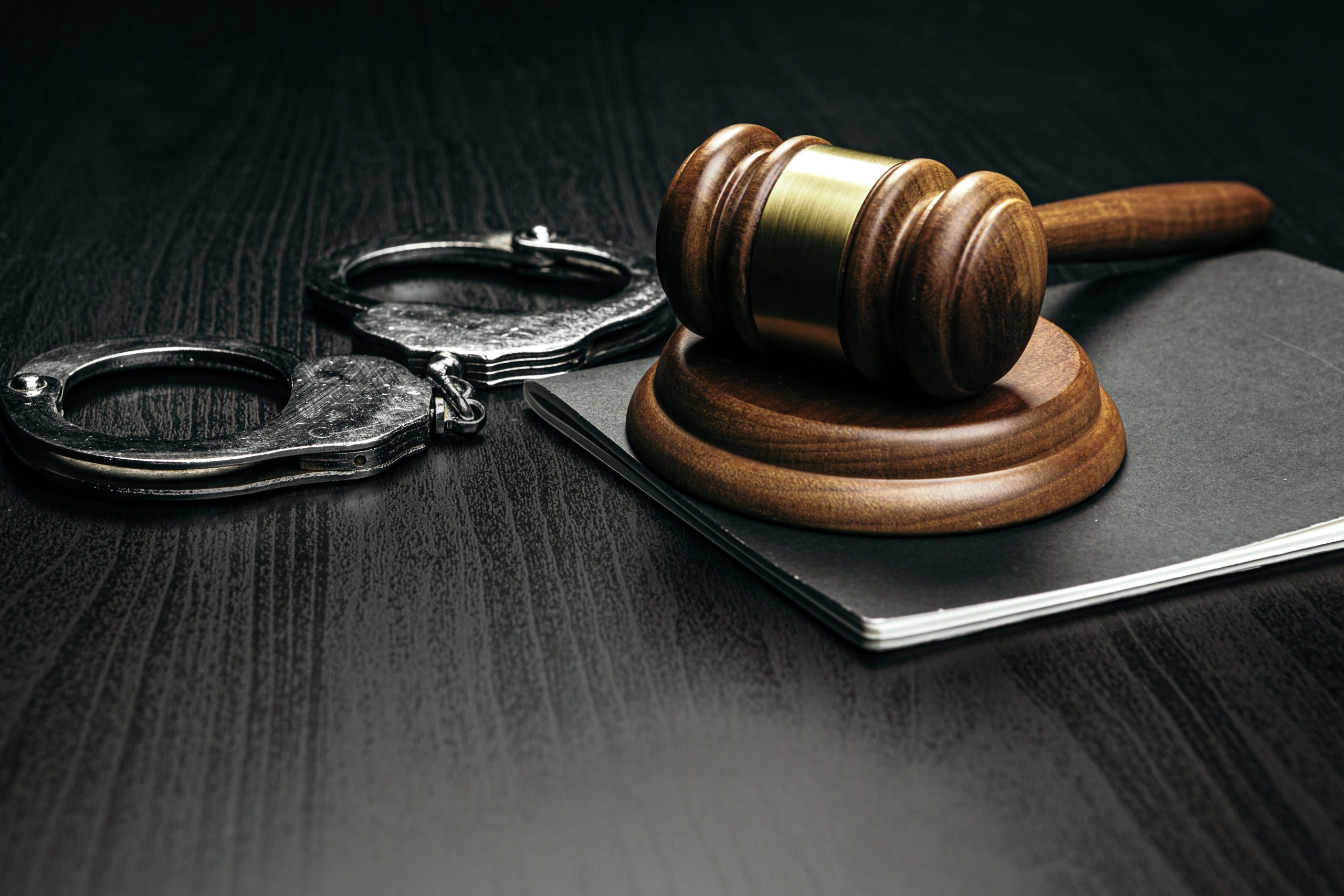 judge-gavel-with-handcuffs-on-wooden-table-35PKRDJ