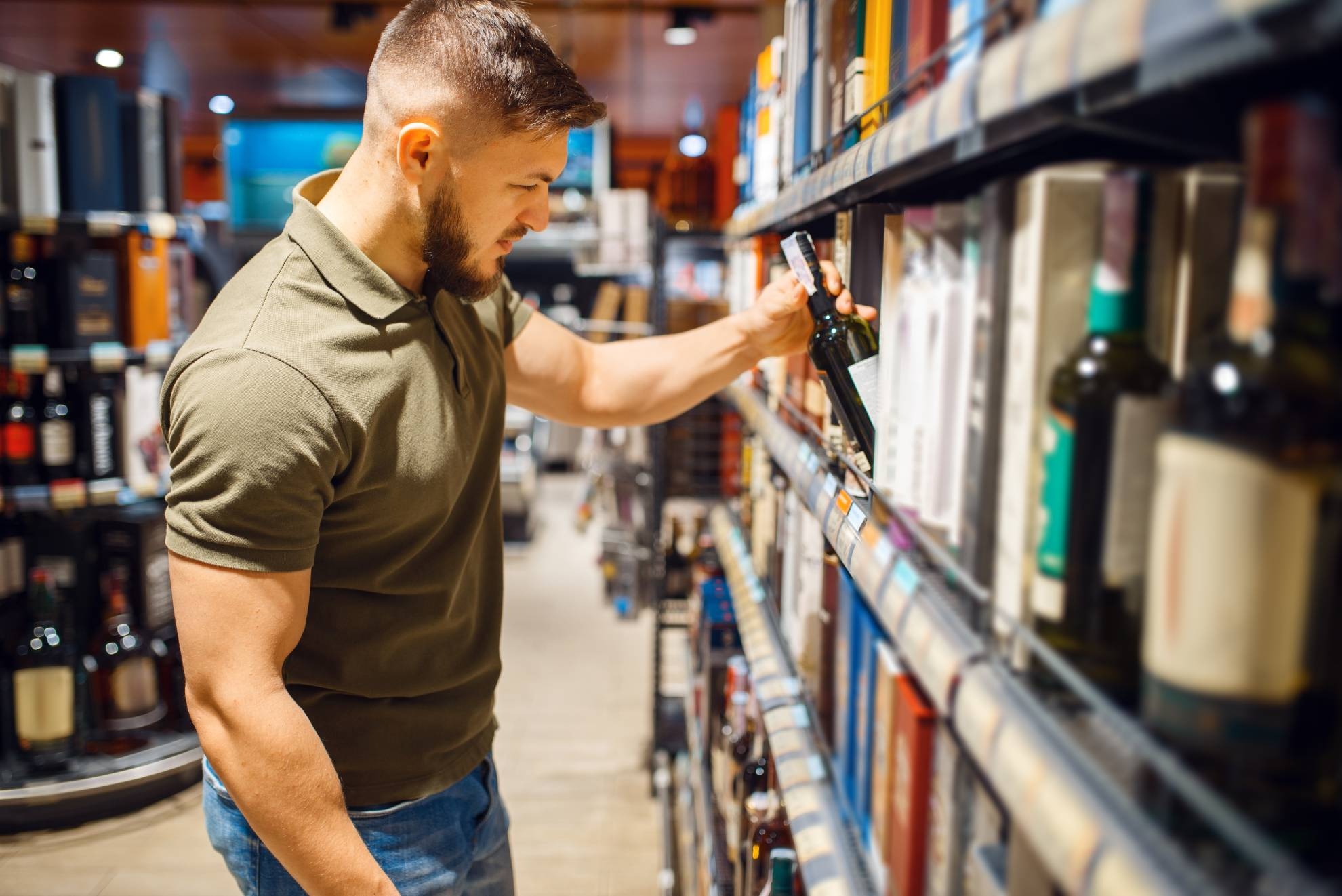 man-choosing-alcohol-products-in-grocery-store-KW7HXQN (1)