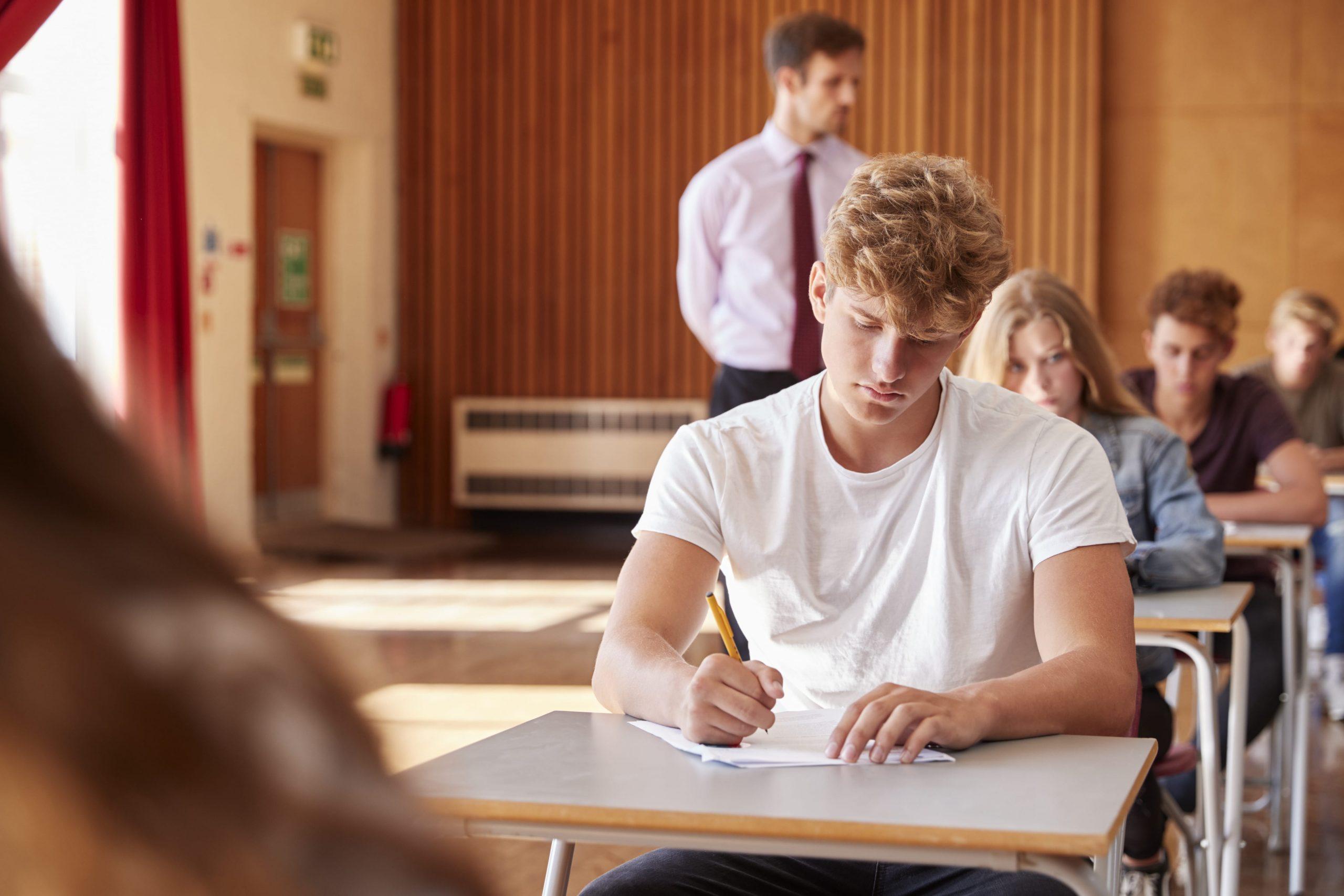 teenage-students-sitting-examination-with-teacher–PBJLET6-min